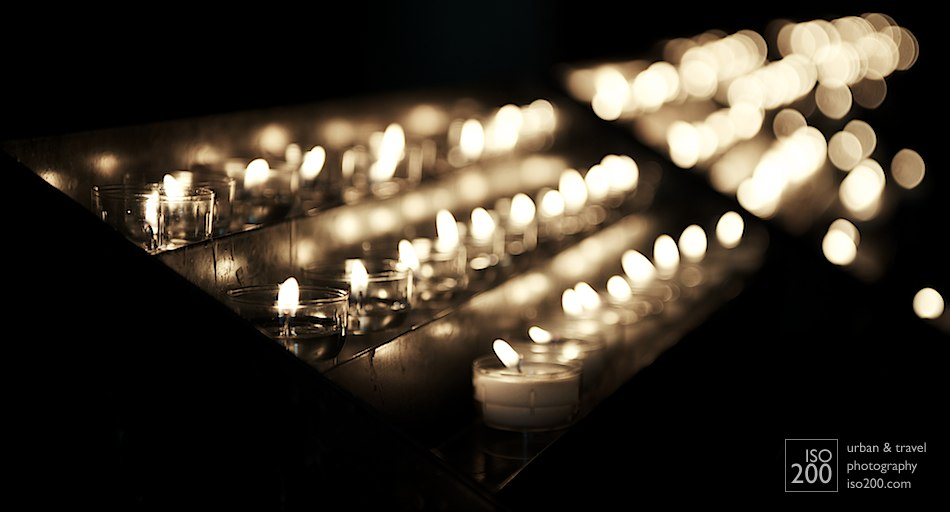 Votive candles flicker in the aisle of the Church of Our Lady, in Brugges, Flanders.