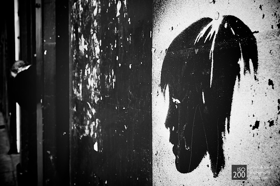 Black and white photo of a spray painted stencil of young boy's head on Bristo Place, just down from the much missed Forest Cafe, Edinburgh. Did you notice the man in the doorway...?